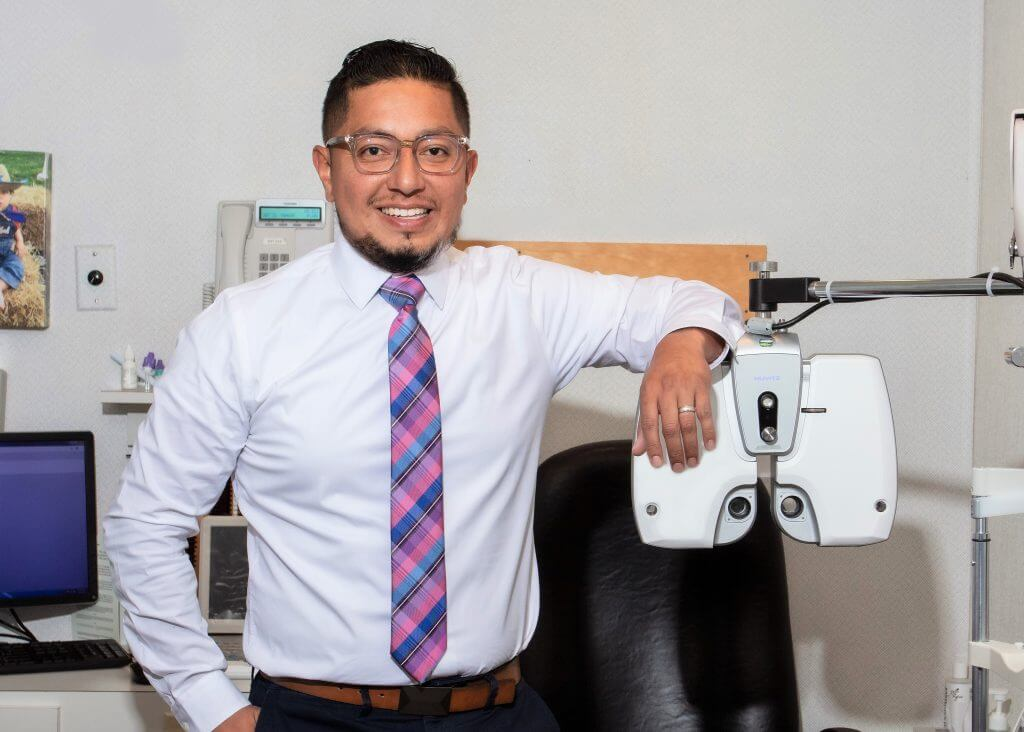 Dr. Fabian Villacis of New Insight Eyecare standing next to his new Huvitz HDR-9000 Digital Refractor in an eye examination room.