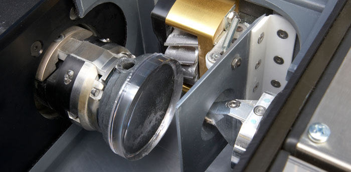 Closeup of a lens blank loaded into the CTL65 Lens Generator by Coburn Technologies. Cutting mechanisms can be seen on the back and side of optical lens blank.