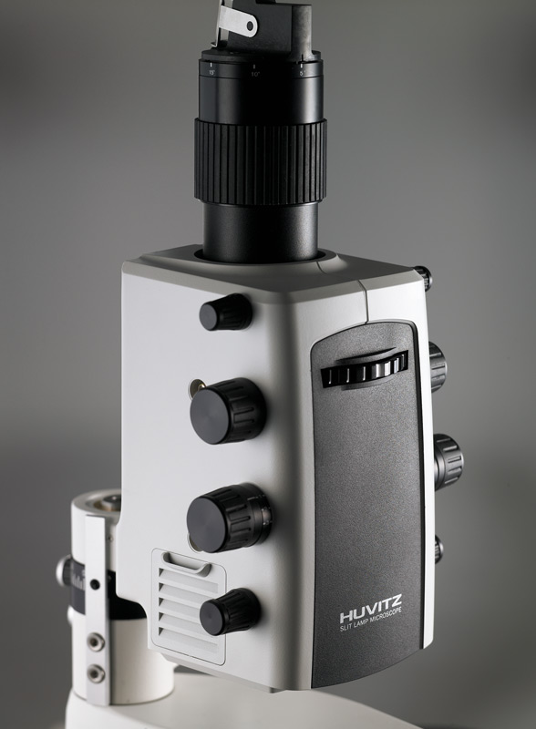Closeup image of the Zeiss integrated illumination unit on the HS-7500 slit lamp by Huvitz. Black and light gray unit with knobs and a dial.