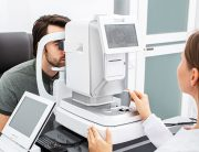 Image of a technician and patient performing an eye exam with an autorefractor. Patient is having his eyes examined through the autorefractive viewfinder. Exam room is white, gray and clean. Exam table also has a digital refractor.